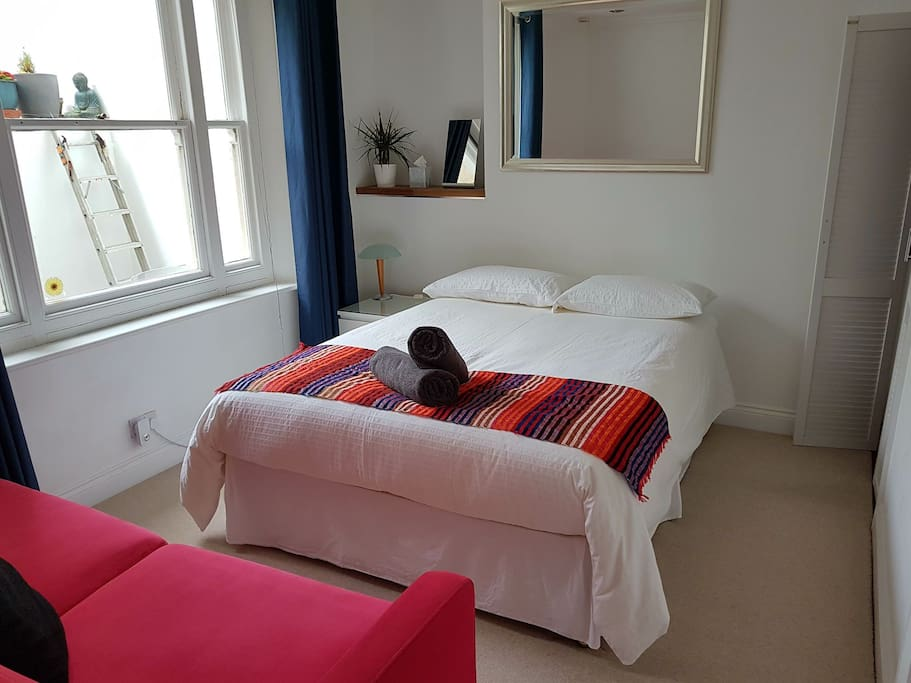 The King-sized bed and sofa overlooking the rear courtyard. Walk-in dressing room to the right, as is the huge ensuite bathroom.