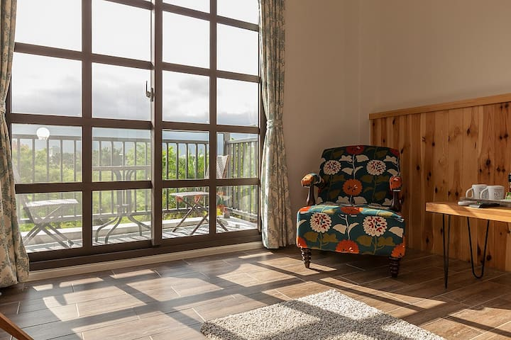 經典雙人房,和妳坐在花布沙發享受整片落地窗的陽光與綠地園景,距夜市10分鐘車程