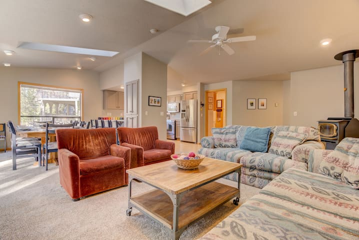 Here's another view of the main level living room with the kitchen and dining area. As you can see the space is open with tall ceilings. Your group can socialize while some cook as others lounge on the couches, watching TV.