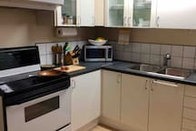 Kitchen with basic amenities including kettle, French press for coffee, pots, plates, cutlery etc.  Full size stove and fridge.  There is a storage room with toaster, blender, picnic cooler, vacuum cleaner and many other items you may need.