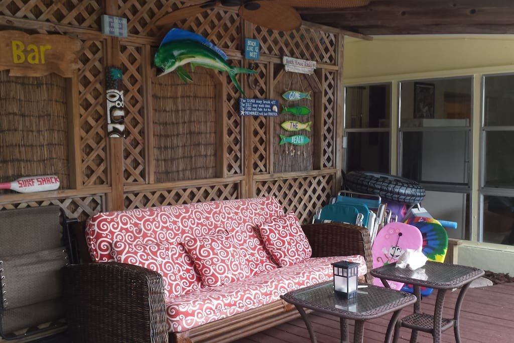 Covered patio area with fun tiki style decor, ceiling fan, lounging, and seating.