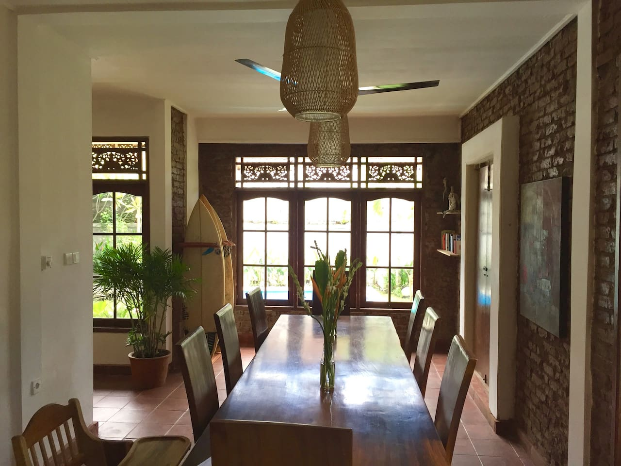 Dining room overlooking the garden on the 1st floor: big teak wood table with 8 chairs, overhead fan and surf rack in the back