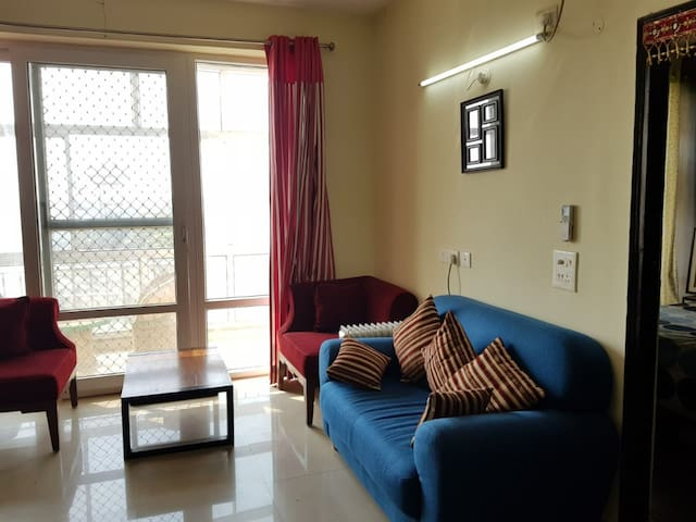 Spacious Living room with attached balcony , Couch & Coffee Table Set Up , Separate Prayer Area with Bhagvat Geeta and other devotional books .