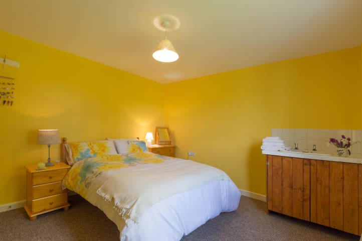 The extremely comfortable queen size bed in the yellow room.