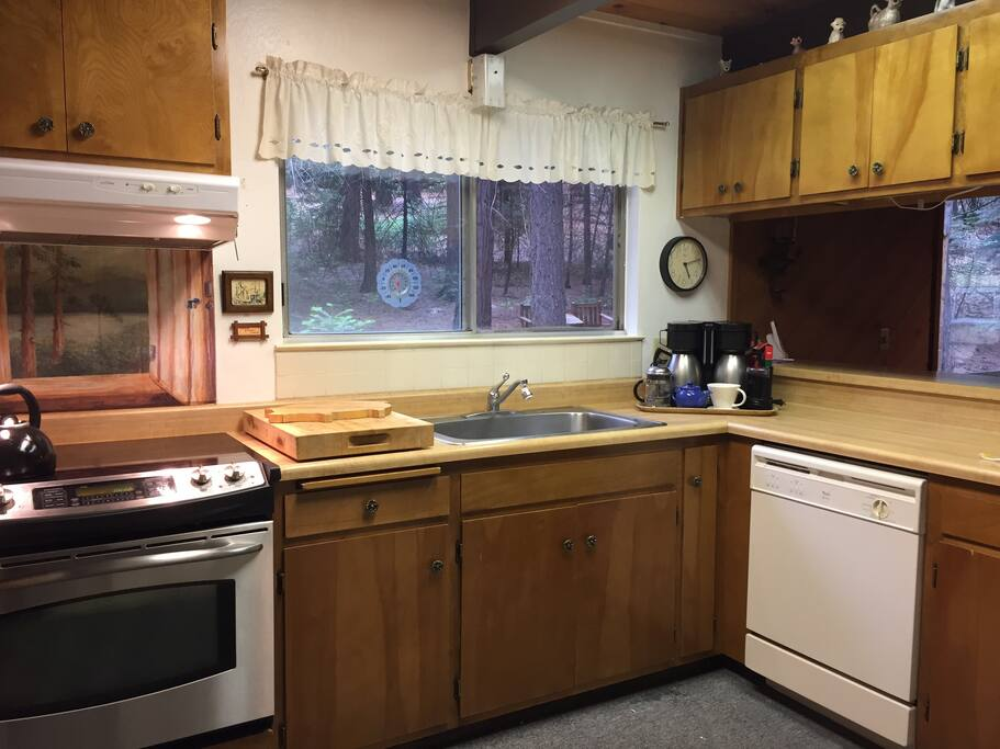 Fully equipped kitchen with dishwasher, stove, oven, refrigerator, blender, food processor, and coffee station.