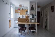 Coin cuisine : table deux foyers induction, combine four micro-onde grill, cafetiere senseo , bouilloire , grille-pain ,frigidaire et machine a laver .