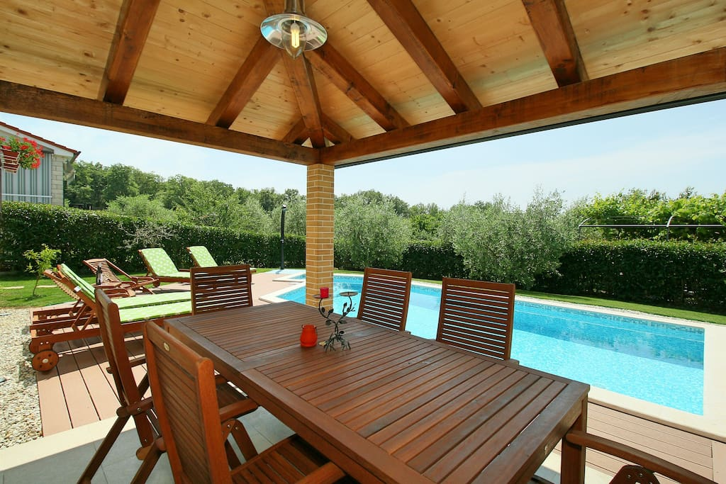 barbecue and dining table overlooking the garden and pool