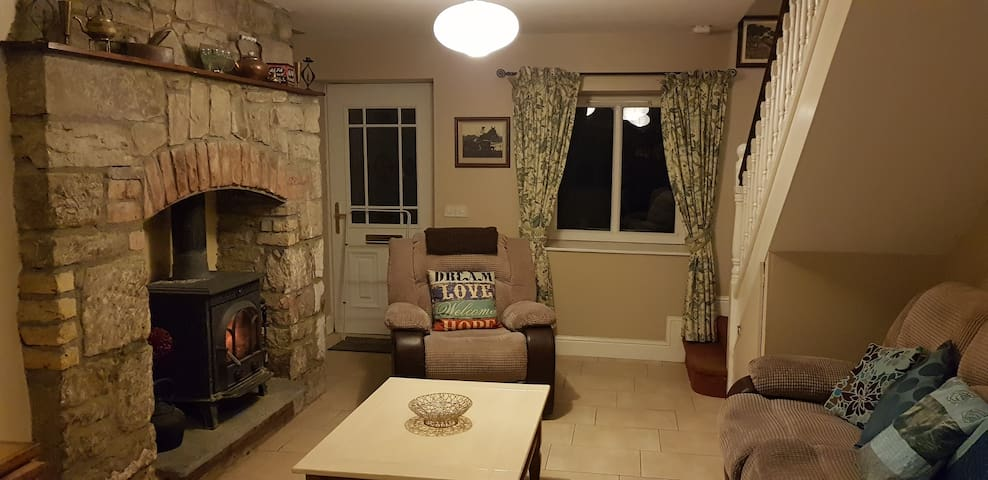 Comfortable sitting area complete with reclining chairs and wood burning stove