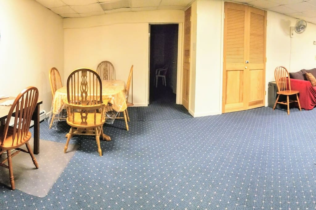 """View when you enter: """"kitchen corner"""" to your left, dining table and entry to a bedroom ahead, and couch with TV to the right."""