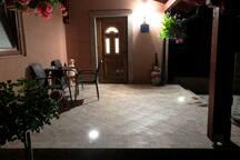 Ulaz i terasa za sobe za iznajmljivanje. Na terasi se nalazi stol sa stolicama.