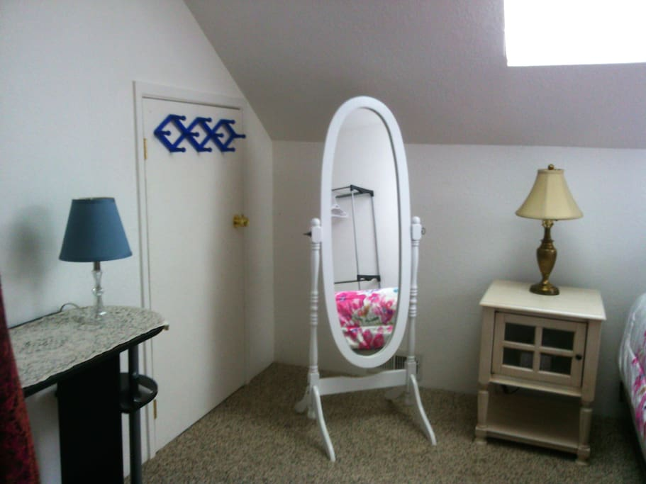 Sturdy pegs and an antique mirror offer additional storage and a complete view of your outfit.