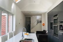 Modern bright sociable living dining entertaining space opening onto private garden