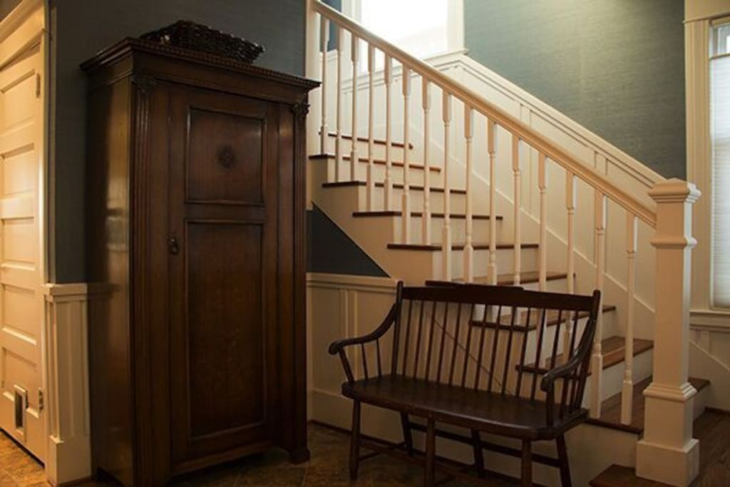 Armoire and stairs leading to full bathroom and 2 bedrooms.