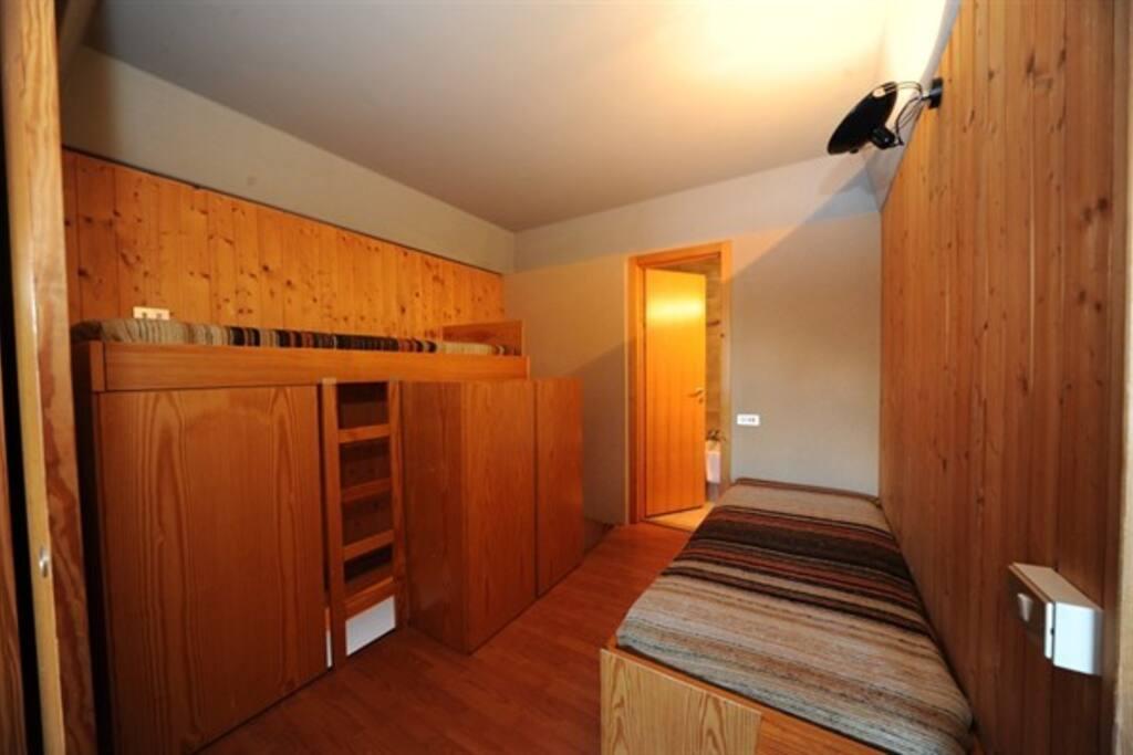 vano al piano superiore con due posti letto e armadi e porta di accesso al bagno