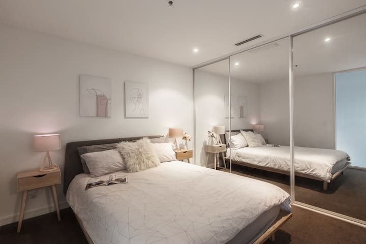 Retreat to a plush queen-sized bed. There is a second TV in the bedroom along with built-in wardrobes for storing your belongings.