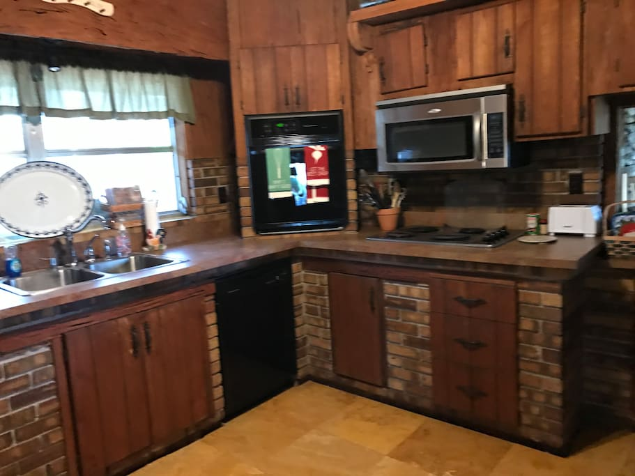 The full kitchen has a double sink, a dishwasher, a microwave, an oven, a refridgerator, a pantry, dishes/utensils, and storage cabinets.