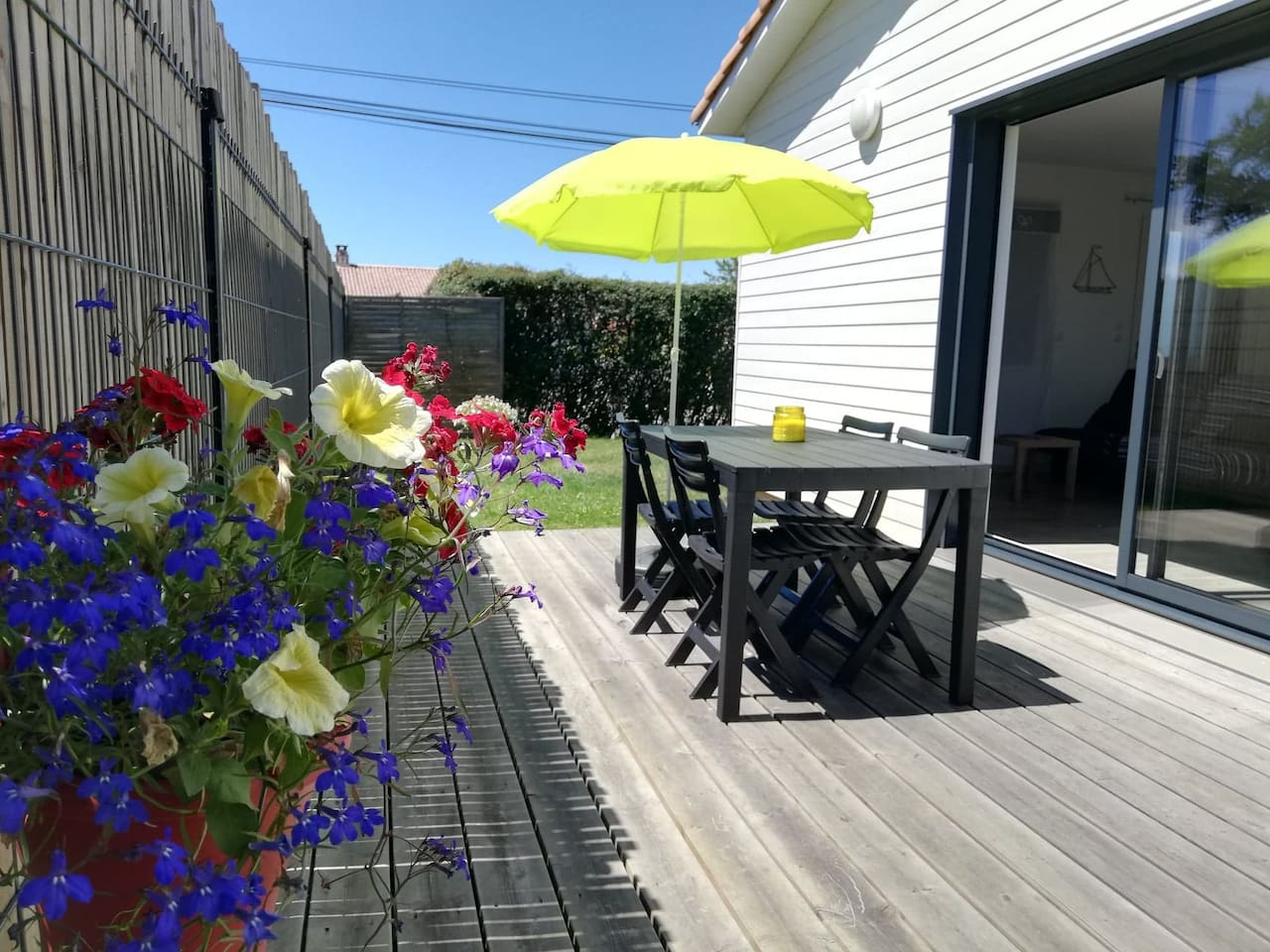 table de jardin sur terrasse bois, parasol, barbecue, 2 chaises longues, sur terrain avec pelouse de 300m2 cloturé sans vis à vis