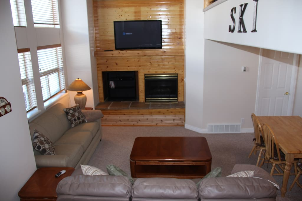 Living space with 2 couches (one sleeper), fireplace and large screen TV