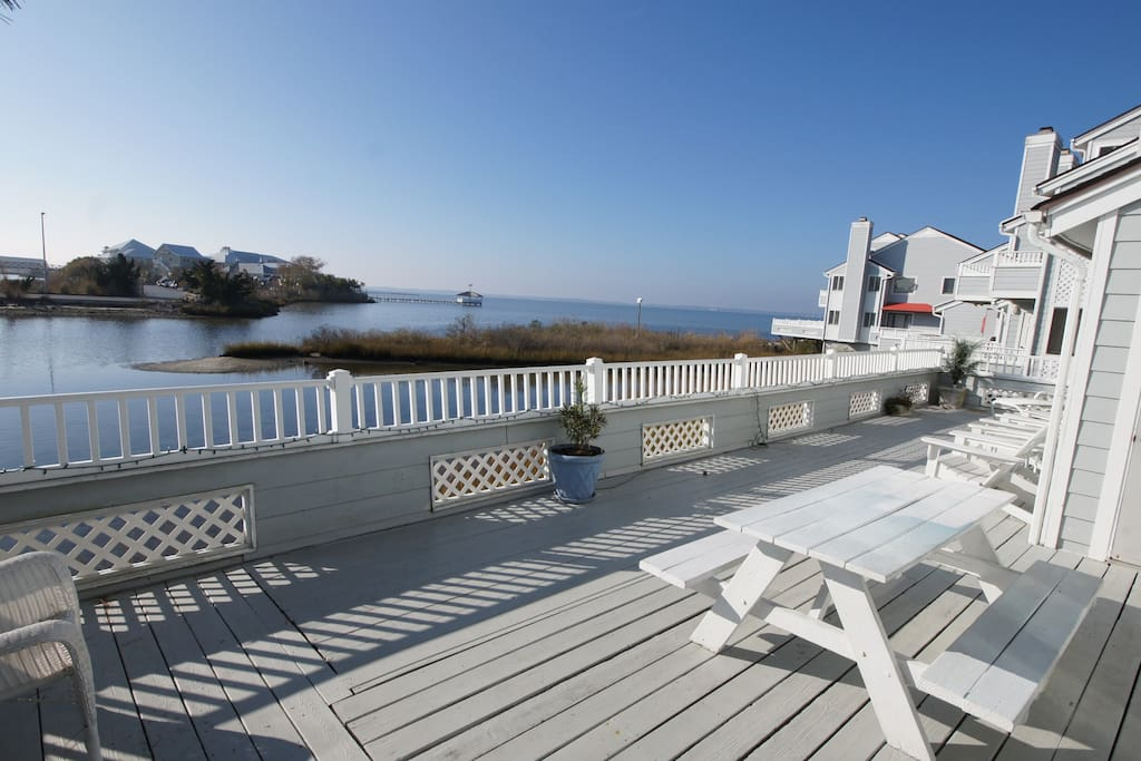 The deck with views of the bay , picnic table ample seating and an awning