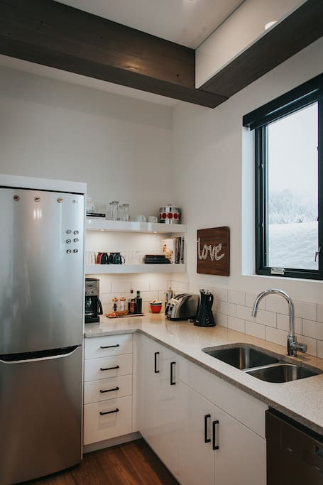 The kitchen has a glass cooktop, oven, microwave, and dishwasher. The fridge has plenty of space for the growler you bought at the Rossland Brewery :) (Fresh Photography)