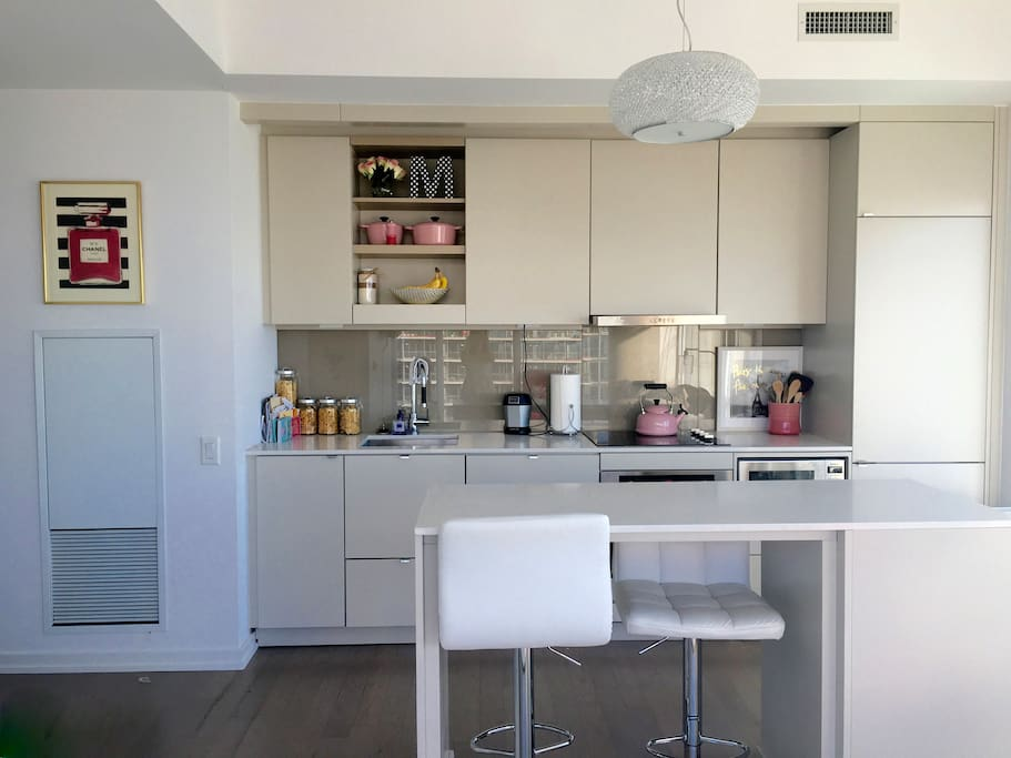 Kitchen with bar stools, microwave, stove top and oven