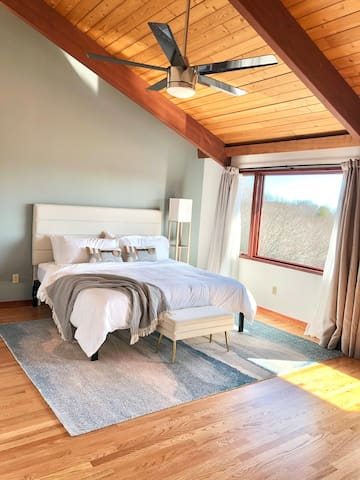 Primary bedroom with a king bed and sweeping views of the ocean and grounds.