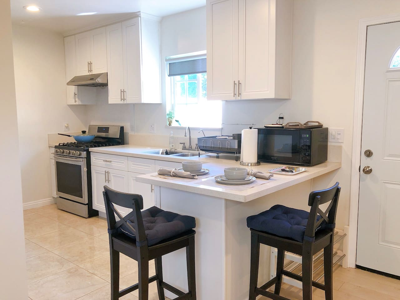 Full-size, fully stocked kitchen with modern appliances including fridge, stove, oven, microwave, and hot water kettle