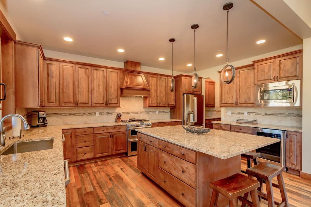 Large granite kitchen with stainless appliances.