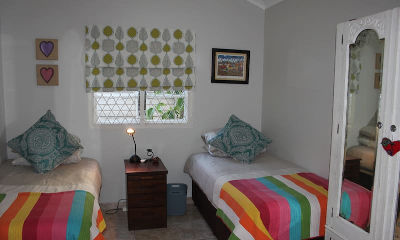 Bedroom 2 - spacious with 2 single beds, ample cupboard space, chest of drawers, bed side table, comfy chair, plenty of mirrors and en-suite bathroom