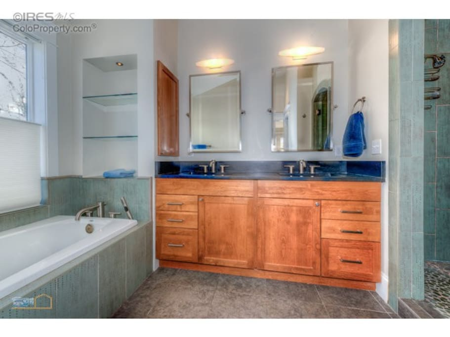 Bathroom w/ cobblestone shower, jacuzzi tub, and double vanity