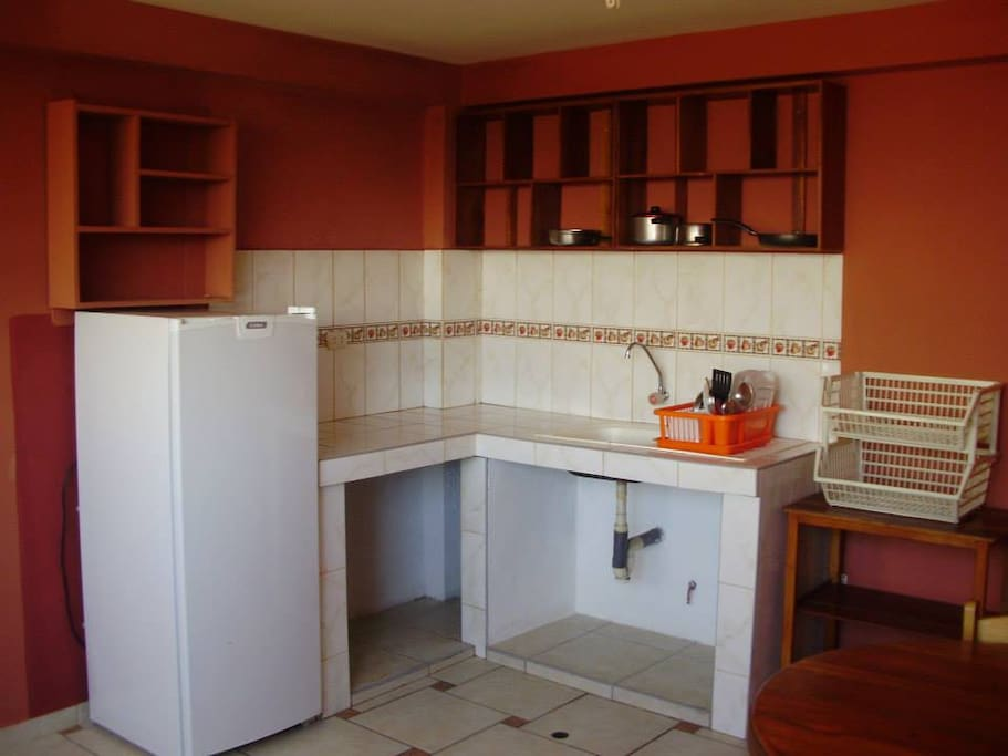Cocineta con refrigerador y utencilios de cocina