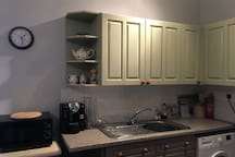 Kitchen area with microwave and coffee machine.