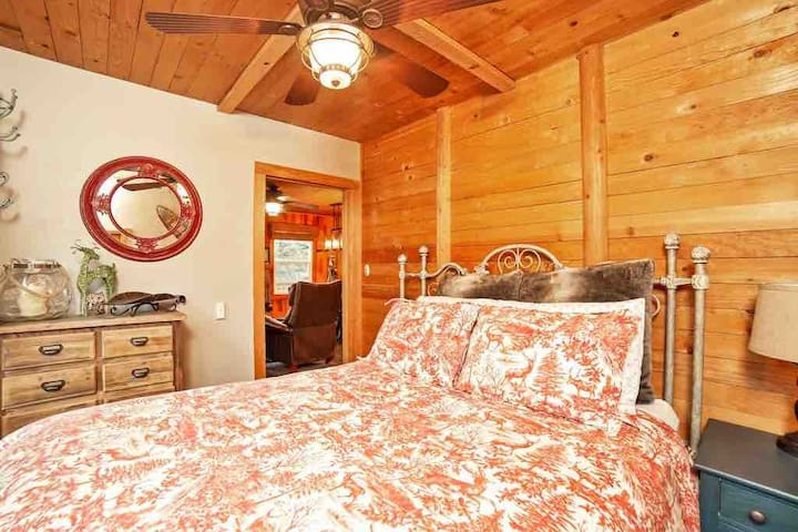 """This the main-floor bedroom, called """"bedroom 1"""" in the listing. The bed is now turned to face the main living-room TV, which is in perfect, full view through the bedroom door. Because watching TV from bed is nice. The remotes also work from bed :-)."""