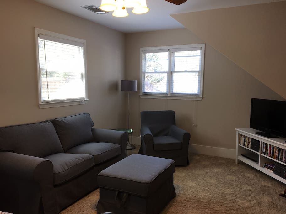 Living area with love seat, ottoman, arm chair and tv