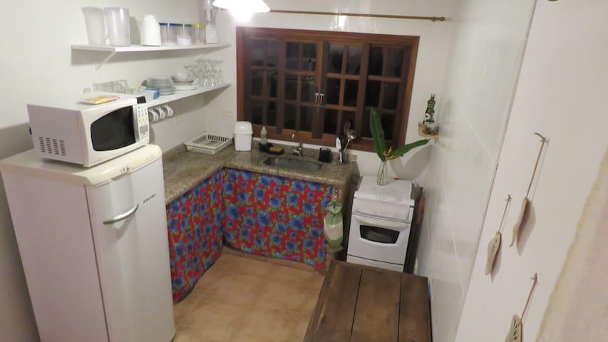 Cozinha completa - geladeira, fogão, microondas, panelas, louça e utensílios.