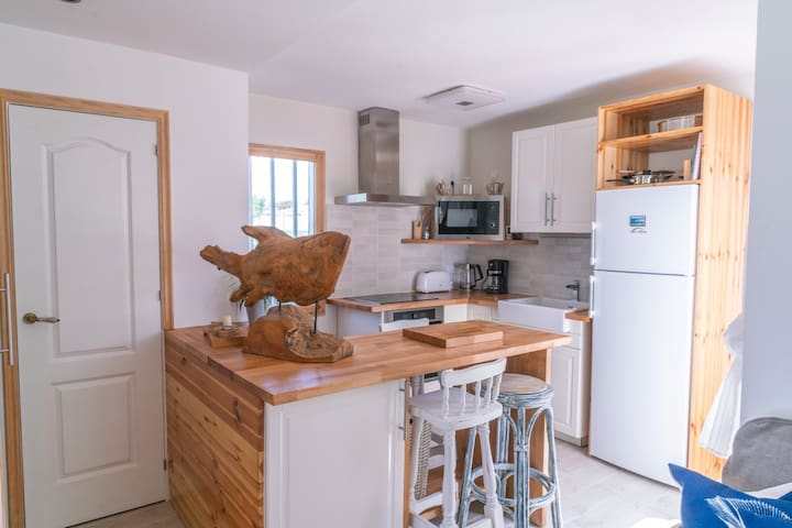 Fully equipped kitchen with sea view, view of the tennis court as well as patio doors leading on to the terrace with garden. View of the swimming pool area from the kitchen