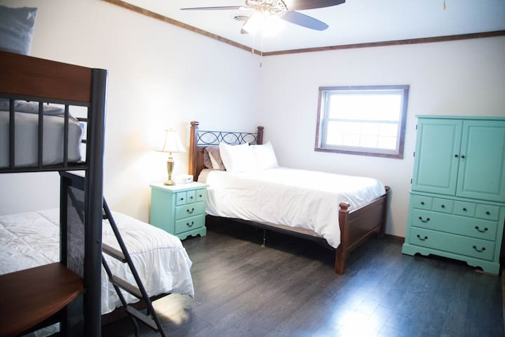 Bunk Room with a full bed, twin bed and queen bed.  Comfortable chair and writing desk.
