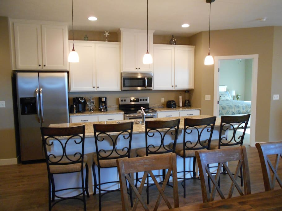 Open kitchen with stainless appliances, toaster, blender, Keurig coffee maker, griddle, crock pot, and plenty of plates, glasses, silverware, and pots and pans.