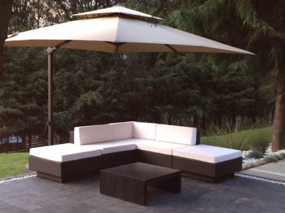 Sala de jardín con mesa de centro y sombrilla