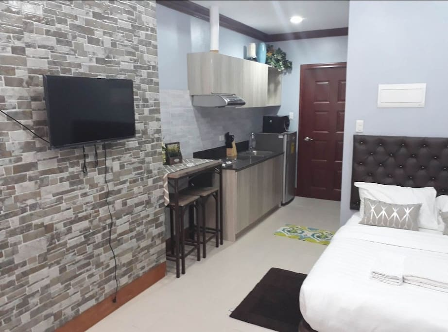 TV, kitchen, entrance door and bed.