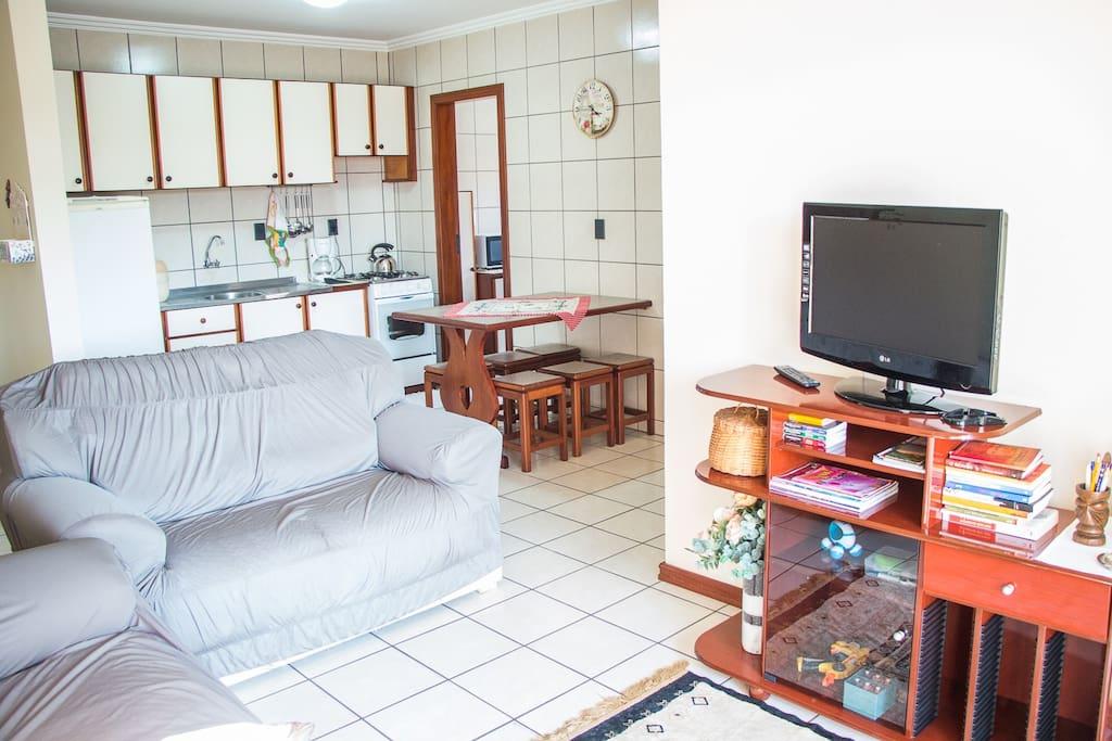 A sala e a cozinha estão integradas em um ambiente só.