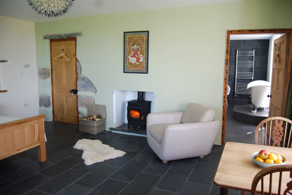 Slate tiled floor with underfloor heating. Wood burner with basket of logs supplied.