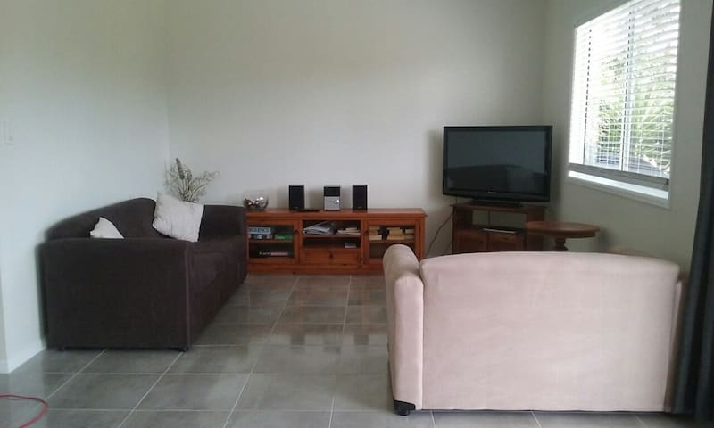 Lounge room with a 3 seater couch that coverts to a sofa bed and a 2 seater couch.