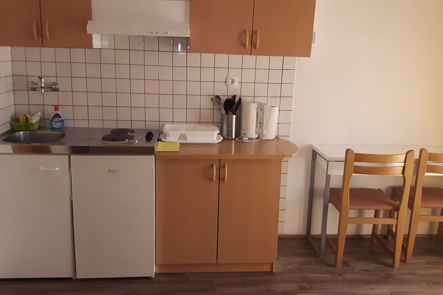 small equipped kitchen, table with two chairs