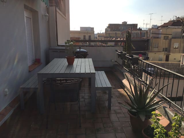 Terrace with afternoon sun, large dining table and BBQ