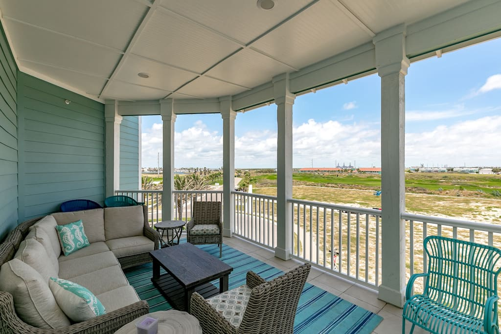 A covered porch offers comfortable seating and a beachside vibe.