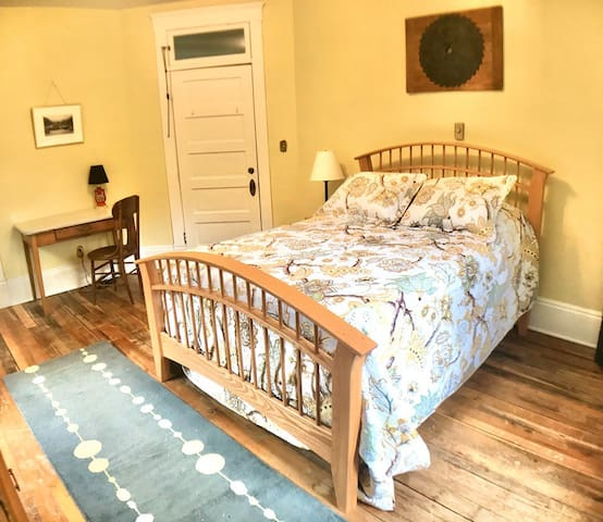 Room 3- The Big Timber Room- features a full-sized bed, a writing desk, 2 beautiful views from 2 windows, and a bathroom shared with others on the same floor.