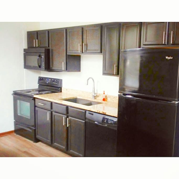 Large kitchen, with some essentials. A pan with utensils, cups, wine glasses, double compartment sink, dishwasher, refrigerator with ice maker.