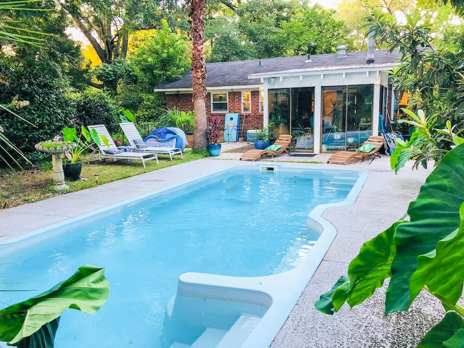 Lush tropical landscaping surrounds you as you lay by the saltwater pool. The pool and backyard are shared with the owners. This view shows the owners house. The Airbnb is to the right (out of frame).
