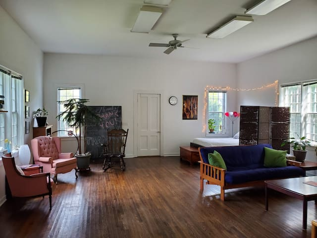 View of the open space: 11ft ceilings provide a lofty feel. Second bed is behind a privacy screen. Futon can be made as a third sleeping arrangement, but space remains for an air mattress if preferred.